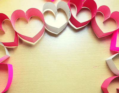 Creating a paper heart chain craft is super simple and a festive way to get excited for Valentine's Day! #Craftsforkids