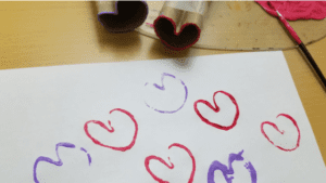 Blog Banner Creating a heart stamp out of a paper roll for Valentine's Day Craft. #Craftsforkids