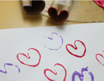 Creating a heart stamp out of a paper roll for Valentine's Day Craft. #Craftsforkids